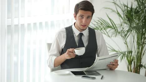 Apuesto-Hombre-Sentado-A-La-Mesa-Tomando-Café-Y-Leyendo-El-Periódico