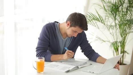 Apuesto-Joven-Estudiando-En-La-Mesa-Con-Libros-Y-Laptop