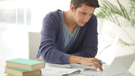 Hübscher-Kerl-Der-Am-Tisch-Mit-Laptop-Studiert-Und-In-Die-Kamera-Lächelt