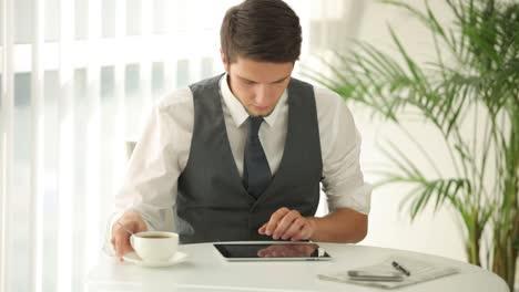 Hombre-Guapo-Sentado-En-La-Mesa-Removiendo-Café-Y-Usando-El-Panel-Táctil