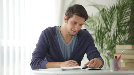 Male-Student-Sitting-At-Table-And-Writing-In-Notebook