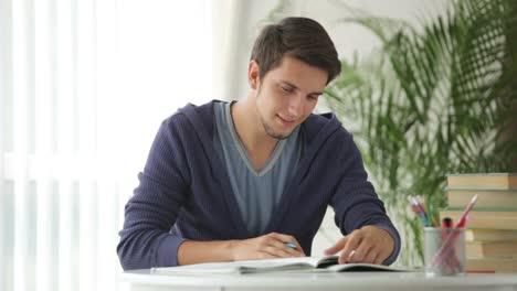 Estudiante-Masculino-Sentado-En-La-Mesa-Y-Escribir-En-El-Cuaderno