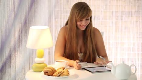 Linda-Chica-Sentada-En-El-Café-Con-Touchpad-Con-Tarjeta-De-Crédito-Mirando-A-La-Cámara