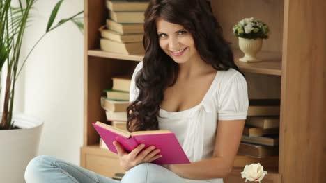 Linda-Chica-Sentada-En-El-Piso-Leyendo-Un-Libro-Mirando-A-Cámara-Y-Sonriendo