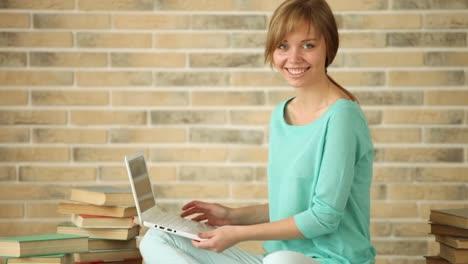 Linda-Chica-Sentada-En-El-Piso-Con-Libros-Usando-Laptop-Mirando-A-La-Cámara