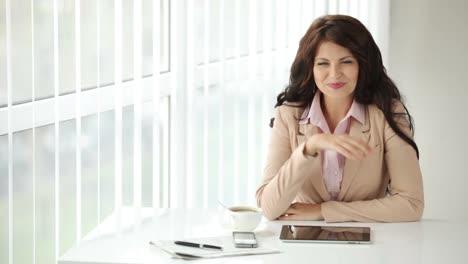 Bastante-Joven-Mujer-Sentada-En-La-Mesa-De-Oficina-Con-Taza-De-Café-Y-Touchpad