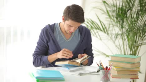 University-Student-Sitting-At-Table-And-Writing-In-Notebook