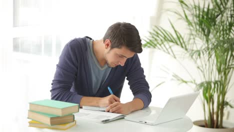 Young-Man-Sitting-At-Table-Studying-With-Books-And-Laptop