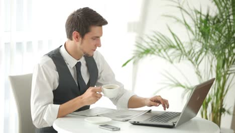 Young-Man-Sitting-At-Table-Using-Laptop-And-Drinking-Coffee