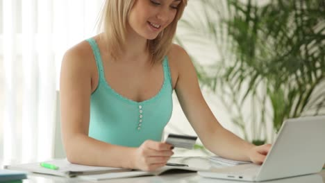 Young-Woman-Sitting-At-Table-Holding-Credit-Card-Using-Laptop-And-Smiling