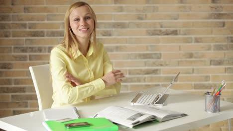 Chica-Atractiva-Sentada-En-La-Mesa-Estudiando-Usando-La-Computadora-Portátil-Mirando-A-La-Cámara