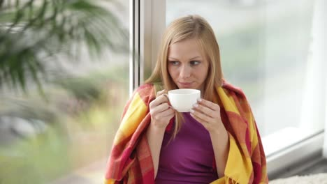 Attractive-Girl-Sitting-By-Window-Drinking-Tea-Looking-At-Camera-And-Smiling-01