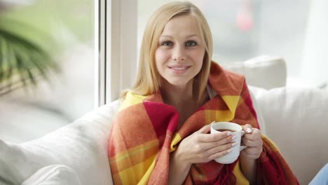 Attractive-Girl-Sitting-On-Sofa-Drinking-Tea-Looking-At-Camera-And-Smiling