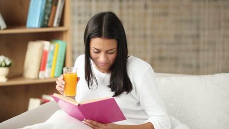 Hermosa-Niña-Sentada-En-El-Sofá-Leyendo-Libro-Bebiendo-Jugo-Mirando-A-La-Cámara-01