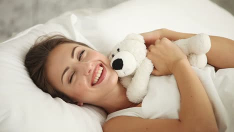 Beautiful-Young-Woman-Lying-In-Bed-Playing-With-Teddy-Bear-And-Smiling-At-Camera