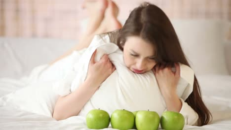 Beautiful-Young-Woman-Lying-In-Bed-With-Apples-In-Front-Of-Her-Looking-At-Cam