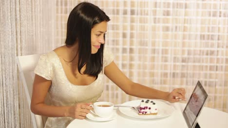Beautiful-Young-Woman-Sitting-At-Cafe-Drinking-Tea-Using-Touchpad-Looking