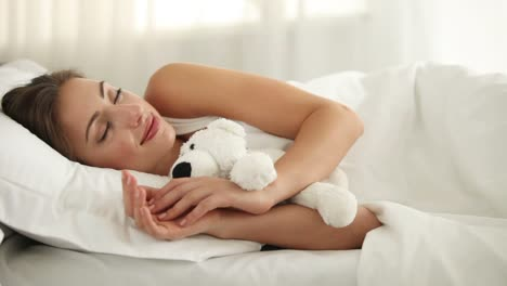 Beautiful-Young-Woman-Sleeping-In-Bed-Hugging-Teddy-Bear-And-Smiling
