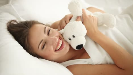 Charming-Girl-Lying-In-Bed-Playing-With-Teddy-Bear-And-Smiling-At-Camera