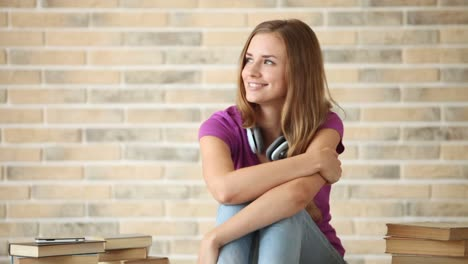 Charming-Girl-Wearing-Headphones-Siting-On-Floor-With-Pile-Of-Books-And-Smiling