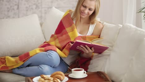 Charming-Young-Woman-Relaxing-On-Couch-Reading-Book-Closing-It-And-Smiling