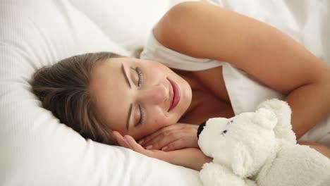 Charmante-Junge-Frau-Die-Im-Bett-Schläft-Aufwacht-Teddybär-Umarmt-Und-Lächelt