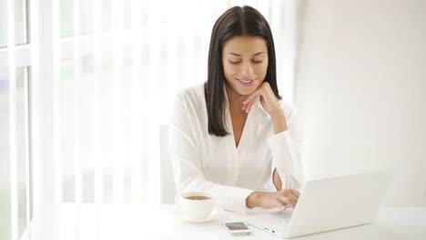 Alegre-Niña-Sentada-En-La-Mesa-De-Oficina-Bebiendo-Té-Usando-Laptop-Mirando
