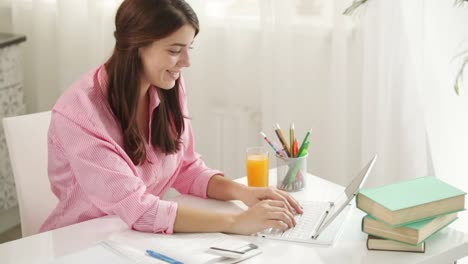 Cheerful-Girl-Sitting-At-Table-Using-Laptop-Holding-Credit-Card