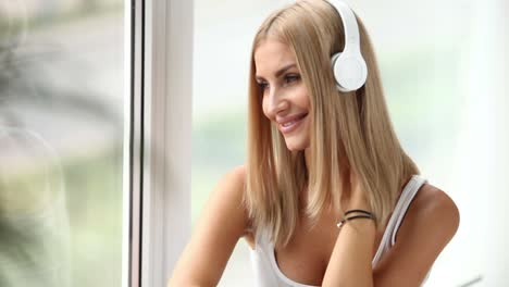 Cheerful-Girl-Sitting-By-Window-Listening-To-Music-With-Headphones-Looking
