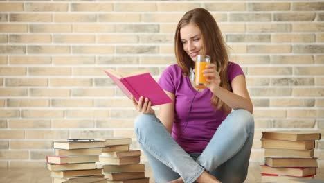 Cheerful-Girl-Sitting-On-Floor-Reading-Book-Drinkng-Juice-And-Smiling-At-Camera