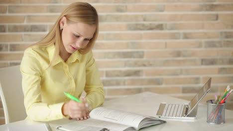 Alegre-Estudiante-Chica-Sentada-En-La-Mesa-Escribiendo-En-El-Cuaderno-Mirando-A-La-Cámara
