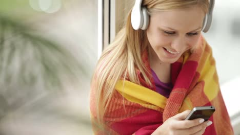 Cute-Girl-In-Headset-Sitting-By-Window-Holding-Cellphone-Looking-At-Camera