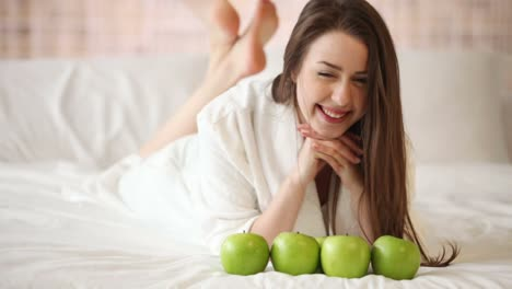 Linda-Chica-Acostada-En-La-Cama-Con-Manzanas-Delante-De-Ella-Contándolas-Mirando