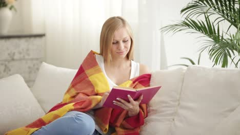 Cute-Girl-Relaxing-On-Sofa-Reading-Book-Looking-At-Camera-And-Smiling-Panning