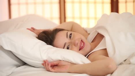 Cute-Girl-Sleeping-In-Bed-Turning-Around-Opening-Her-Eyes-Smiling-At-Camera