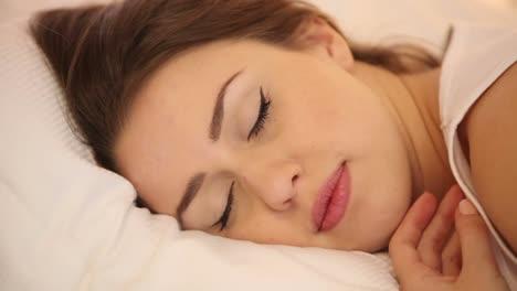 Linda-Chica-Durmiendo-En-La-Cama-Despertando-Mirando-A-Cámara-Y-Sonriendo