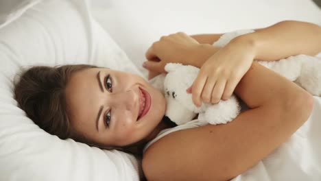 Cute-Young-Woman-Lying-In-Bed-Playing-With-Teddy-Bear-And-Smiling-At-Camera