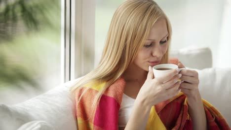 Cute-Young-Woman-Sitting-On-Sofa-Drinking-Tea-From-Cup-Looking-At-Camera-And