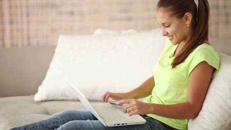 Pretty-Girl-Sitting-On-Sofa-With-Laptop-Holding-Credit-Card-And-Smiling-02