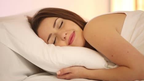 Linda-Chica-Durmiendo-En-La-Cama-Abriendo-Los-Ojos-Y-Sonriendo-A-La-Cámara-Panorámica