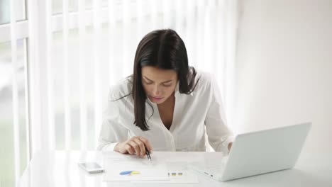 Pretty-Young-Woman-Sitting-At-Office-Desk-Working-Using-Laptop-Looking-At-Camera