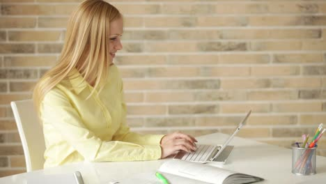 Bastante-Joven-Mujer-Sentada-En-La-Mesa-Usando-Laptop-Con-Tarjeta-De-Crédito-Mirando