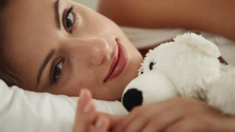Young-Woman-Lying-In-Bed-Hugging-Teddy-Bear-Looking-At-Camera-And-Smiling