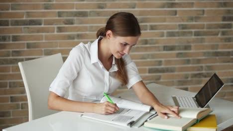 Mujer-Joven-Sentada-En-El-Escritorio-Escribiendo-En-El-Libro-De-Trabajo-Usando-La-Computadora-Portátil-Mirando-A-La-Cámara