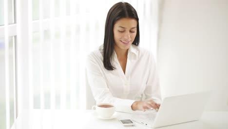 Mujer-Joven-Sentada-En-El-Escritorio-De-Oficina-Usando-Laptop-Bebiendo-Té-Y-Sonriendo
