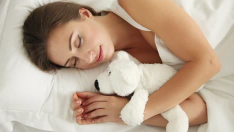 Young-Woman-Sleeping-In-Bed-Hugging-Teddy-Bear-Waking-Up-Looking-At-Camera
