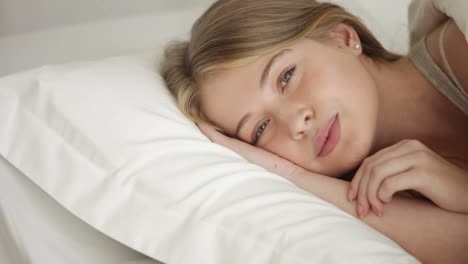 Attractive-Young-Woman-Sleeping-In-Bed-Opening-Her-Eyes-Looking-At-Camera