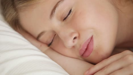 Attractive-Young-Woman-Sleeping-In-Bed-Waking-Up-Looking-At-Camera-And-Smiling