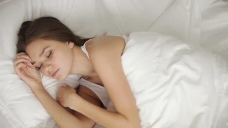 Schöne-Junge-Frau-Die-Im-Bett-Schläft-Aufwacht-Und-In-Die-Kamera-Schaut-Und-Lächelt