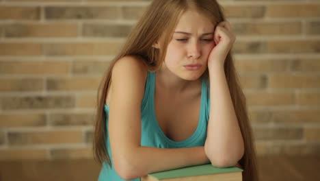 Gelangweiltes-Mädchen-Das-Mit-Einem-Stapel-Bücher-Auf-Dem-Boden-Sitzt-Und-Die-Kamera-Schwenkt